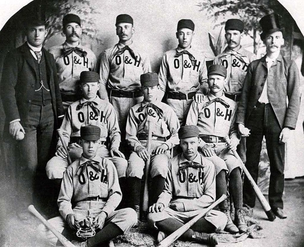 Antique photo with nine baseball players and two coaches.