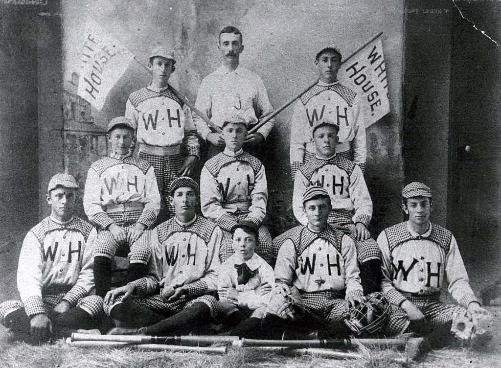 Antique photo of nine baseball players, one coach and a mascot.
