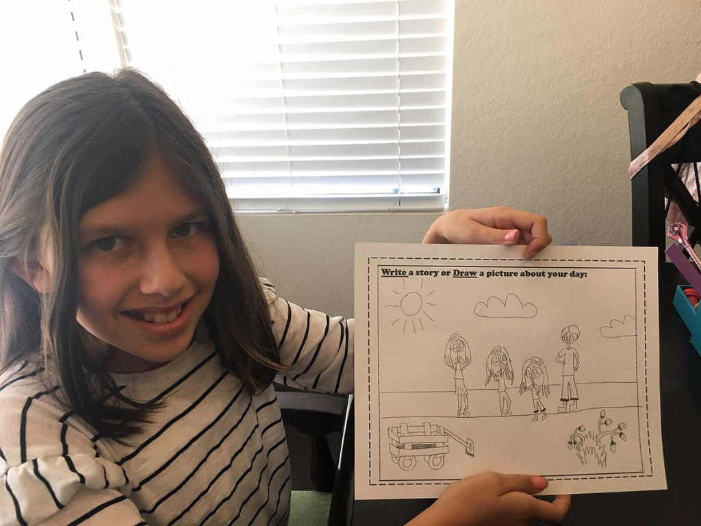 photo of a girl who has drawn a picture of a moment in her day.