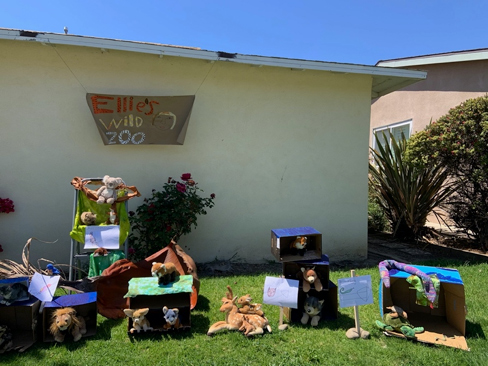 "photo of yard with stuff animals arranged in cardboard boxes and a sign that reads ""Ellie's Wild Zoo"""