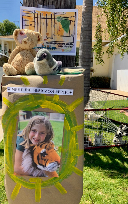 "photo of a yard, in the foreground is a painted cardboard box that says ""Meet the Head Zookeeper"". On the box is a photo of a girl holding a stuffed tiger."
