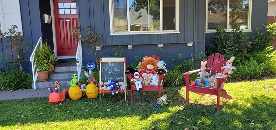 "photo of a front yard with stuffed animals arranged on chairs. A sign says ""The Friendly Zoo""."