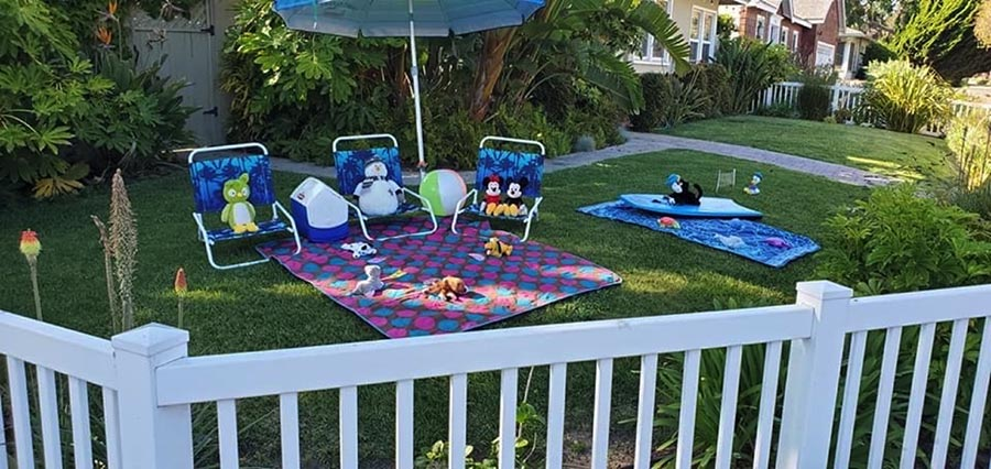 photo of a backyard with stuff animals arranged on chairs